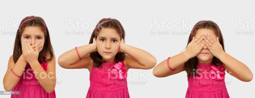 Little girl imitating Three wise monkeys stock photo
