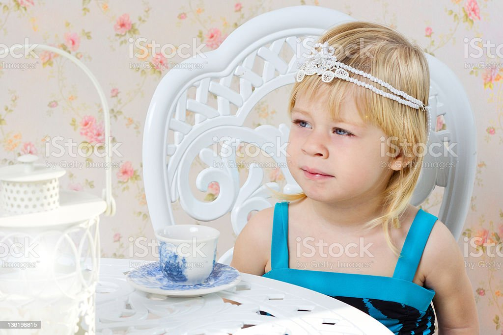 Little girl in a beautiful dress drinking tea royalty-free stock photo