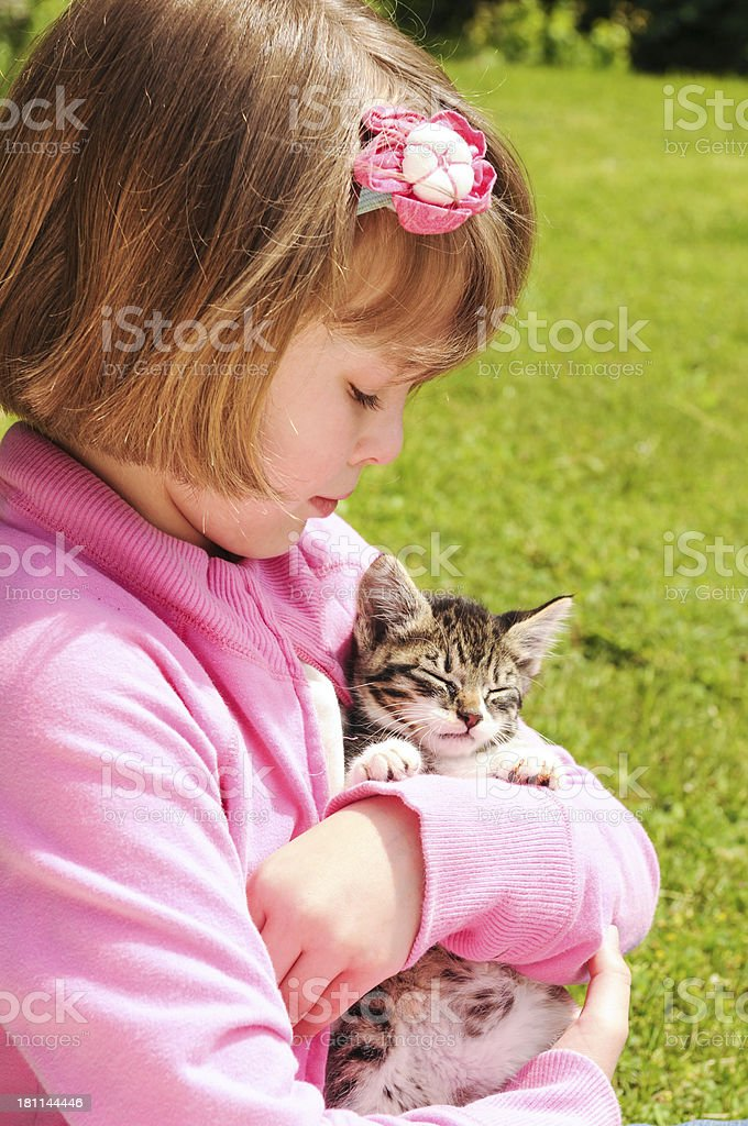 Little Girl in a Pink Sweater Holding Pet Kitten royalty-free stock photo