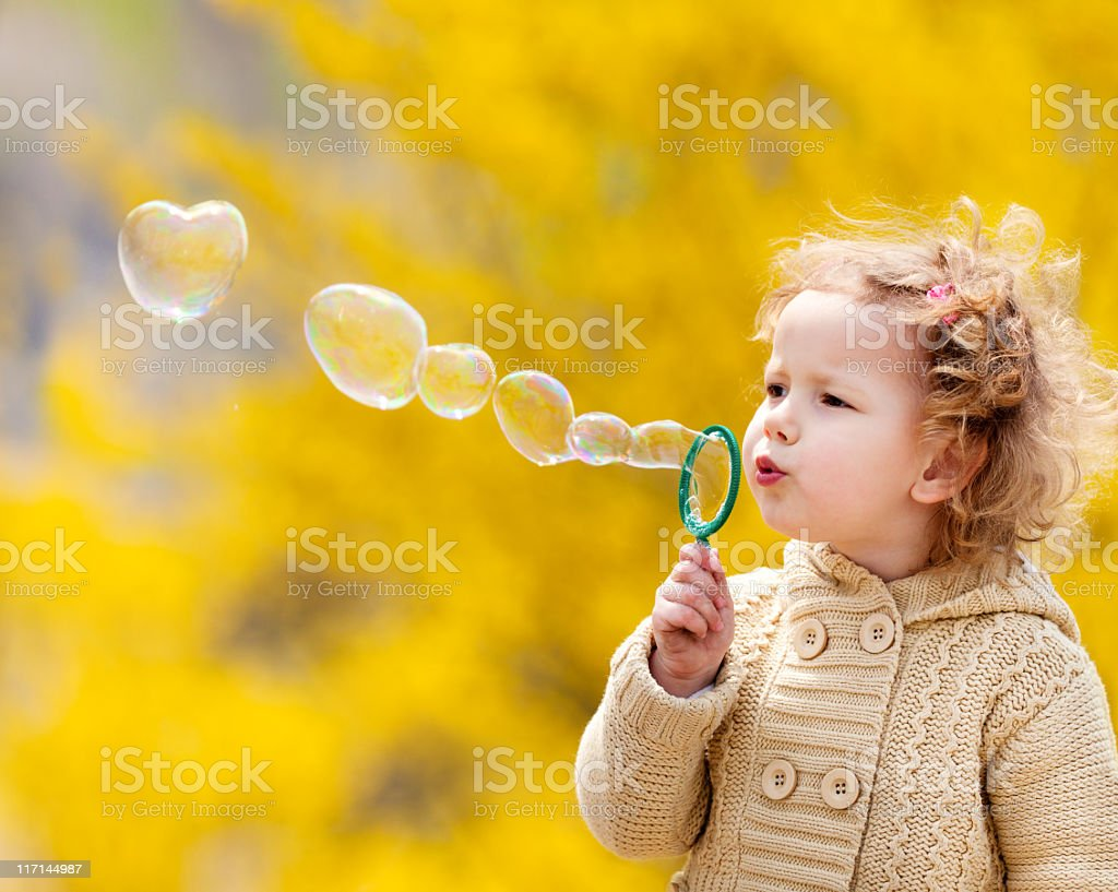 A little girl in a tan sweater blowing bubbles stock photo