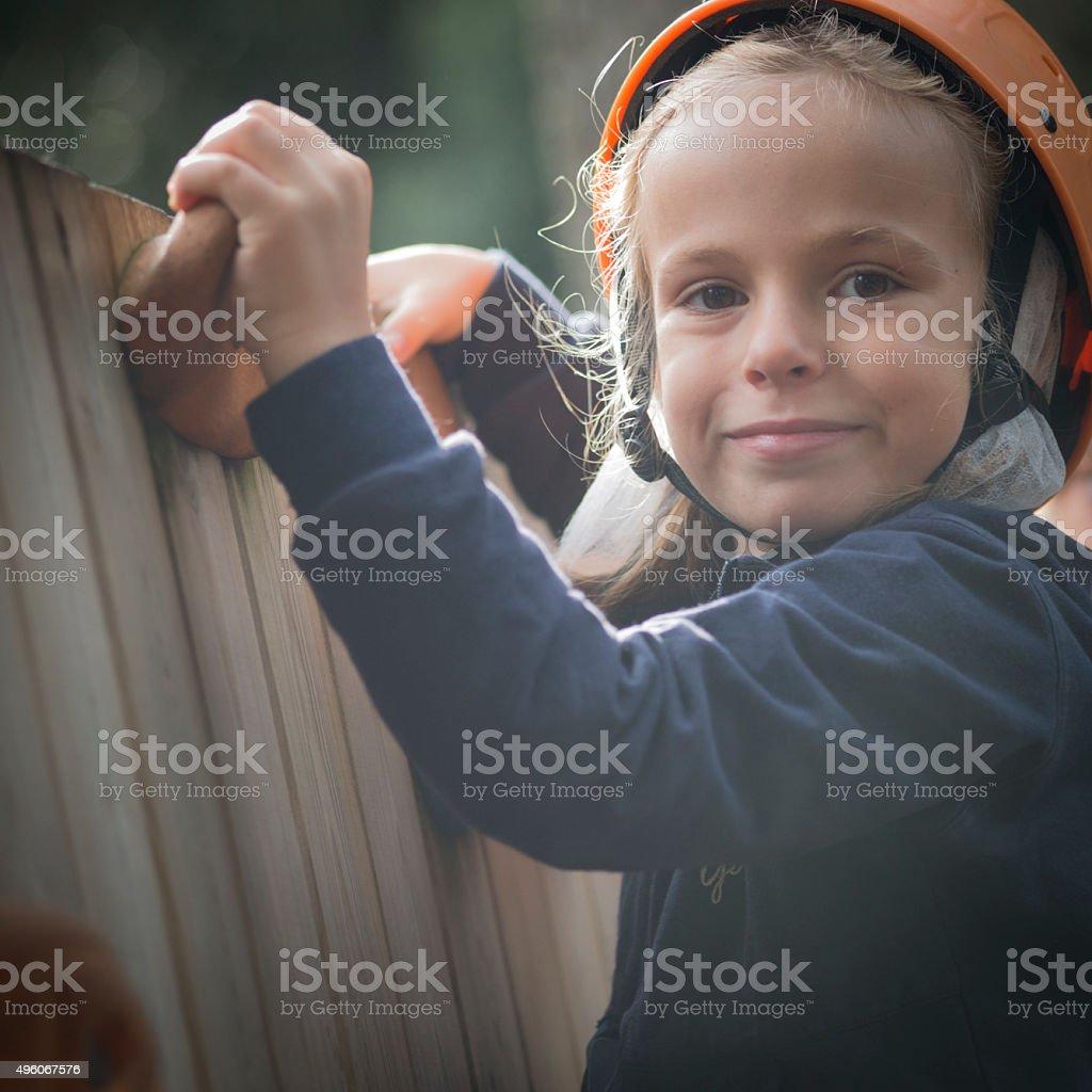 Little Girl in Adventure Park Climbing on a Wooden Wall stock photo