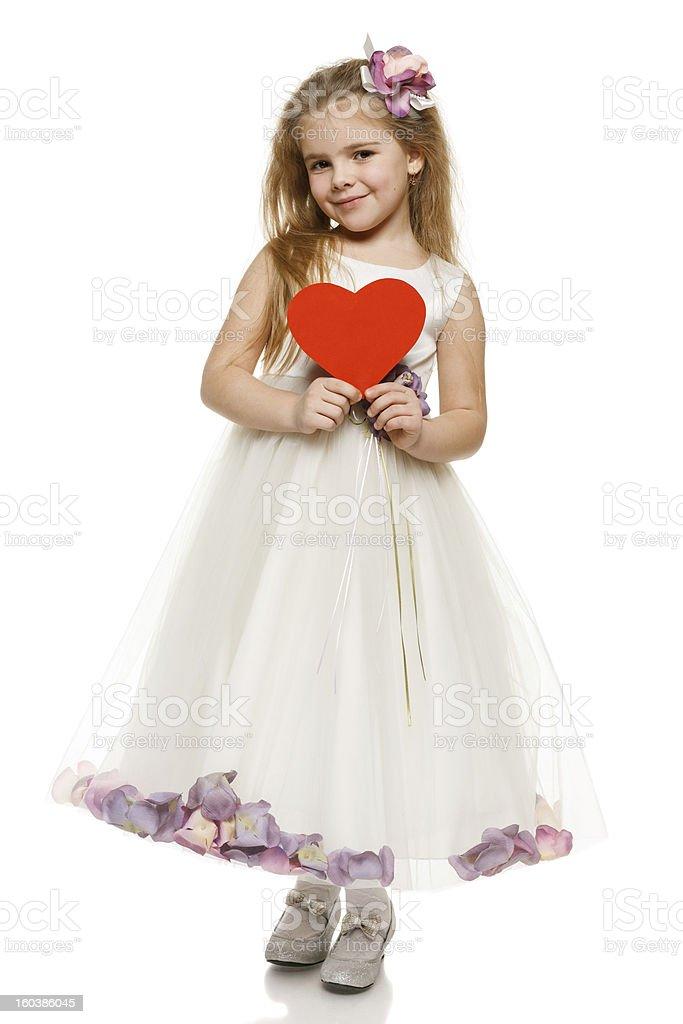 Little girl in beautiful dress holding heart shape royalty-free stock photo