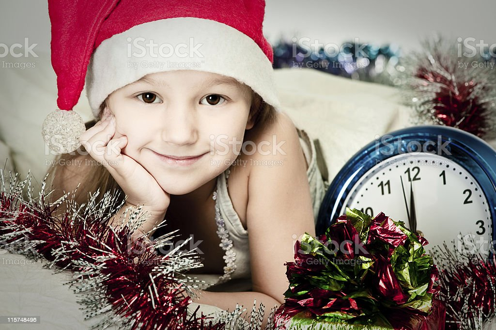 Little girl in bed waiting for the midnight royalty-free stock photo