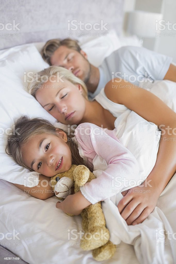Little girl in bed with her parents royalty-free stock photo