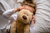 little girl in bed with soft toy the emotions