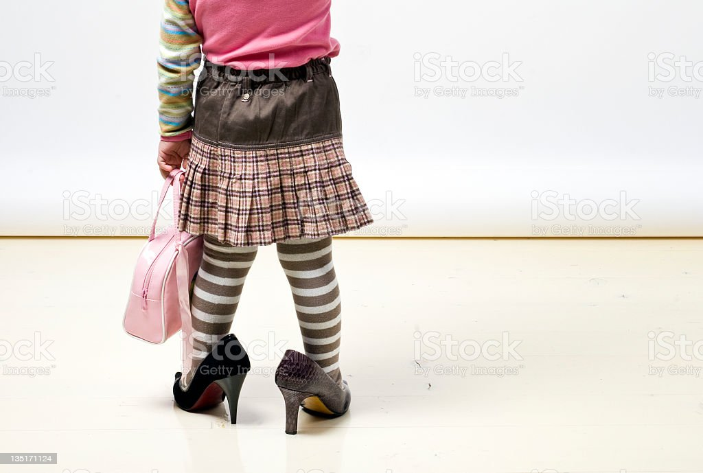 Little girl in big shoes stock photo