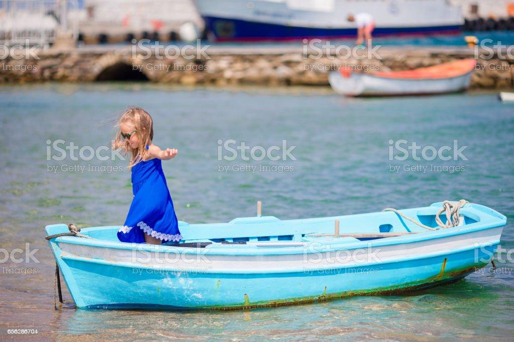 Little girl in blue boat in the sea bay near Mykonos in Greece. Little kid enjoy swimming in the small boat. stock photo
