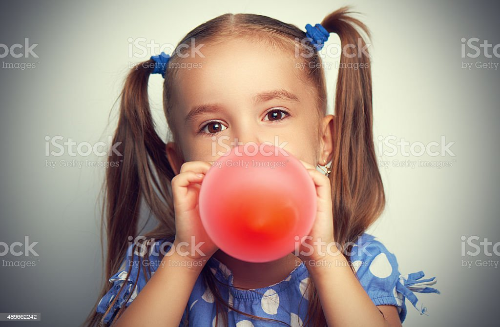 little girl in blue dress inflates red balloon stock photo