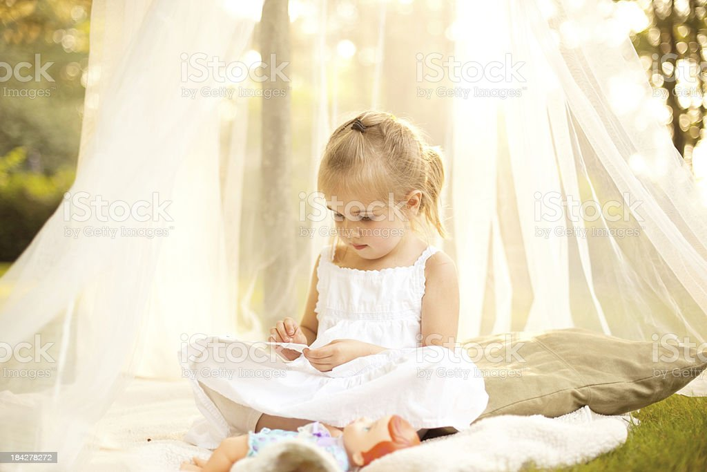 Little Girl in Canopy Under Tree with Doll royalty-free stock photo
