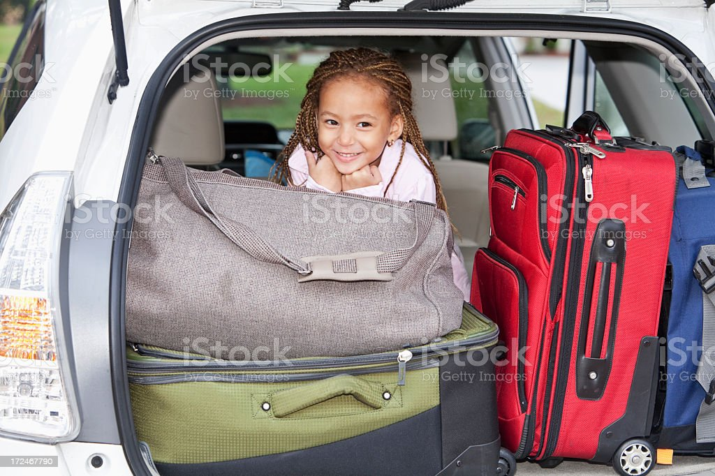 Little girl in car packed for trip stock photo