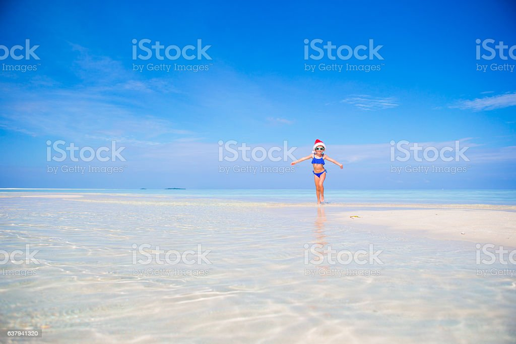 Little girl in Christmas hat on white beach during Xmas stock photo