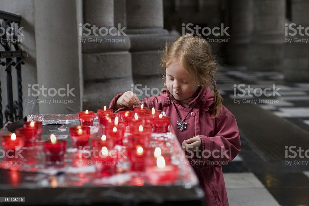 Little girl in church, lighting a candle royalty-free stock photo