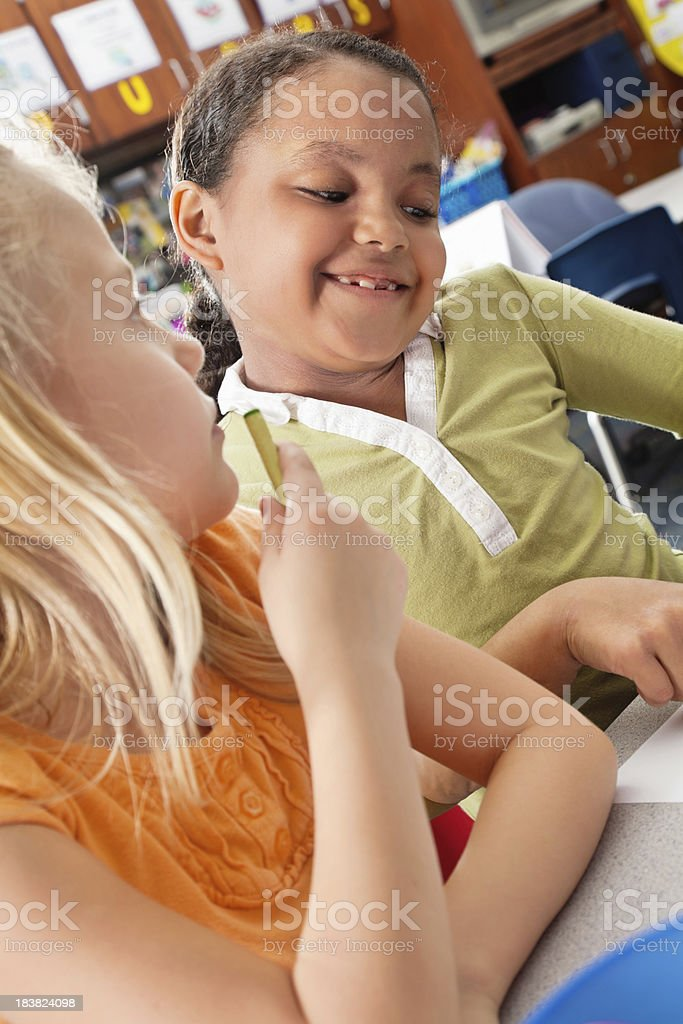 Little Girl in Class With Friend Looking at Work royalty-free stock photo