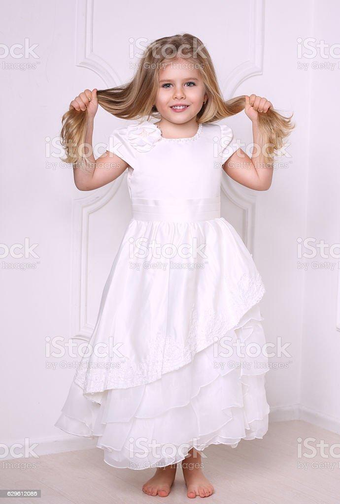 Little girl in dress holding her hair. White background stock photo