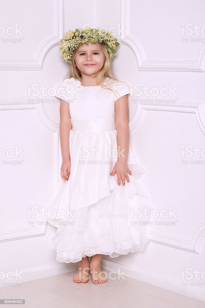 Little girl in dress with head wreath. White background stock photo