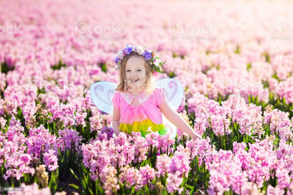 Little girl in fairy costume playing in flower field royalty-free stock photo