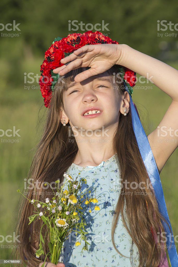 Little girl in field sad looking at the sky stock photo