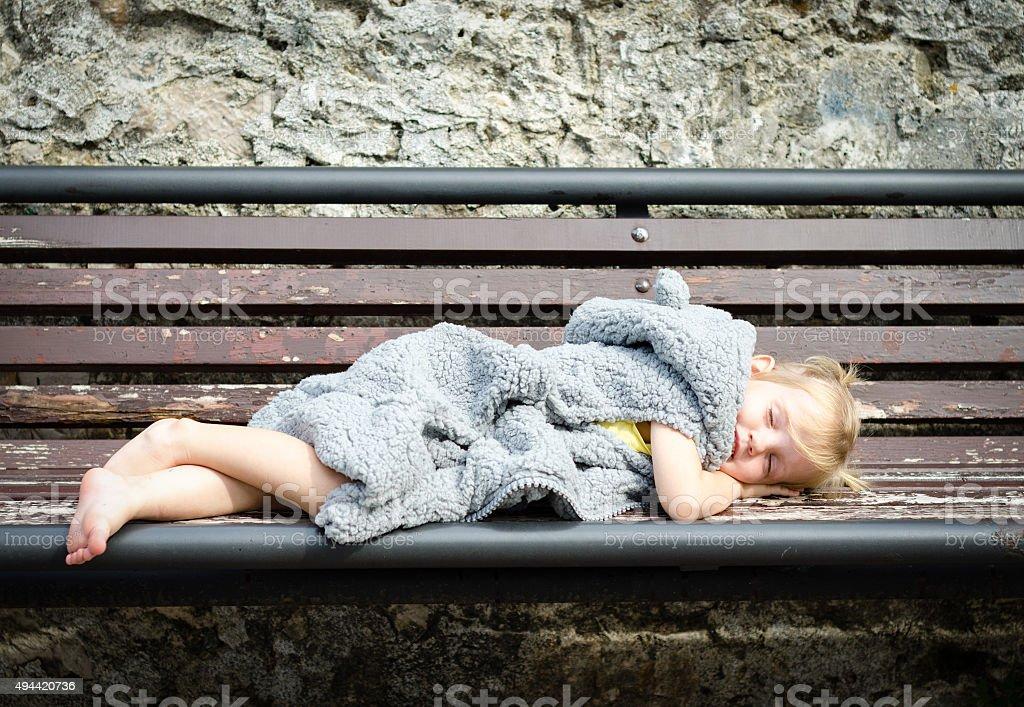 little girl in fur coat sleeping on the bench stock photo
