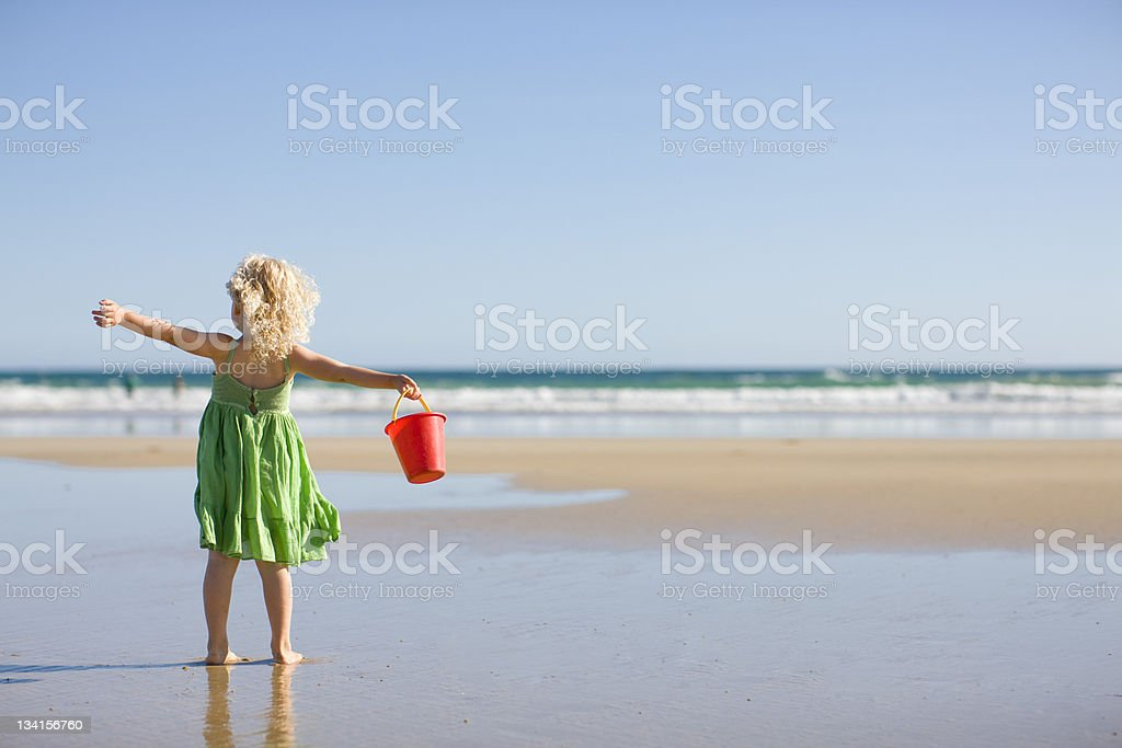 Little girl in green dress holding red bucket at the beach stock photo
