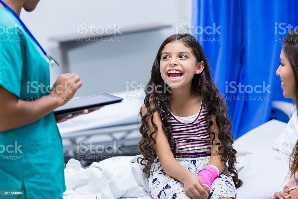Little girl in hospital emergency room with broken arm stock photo