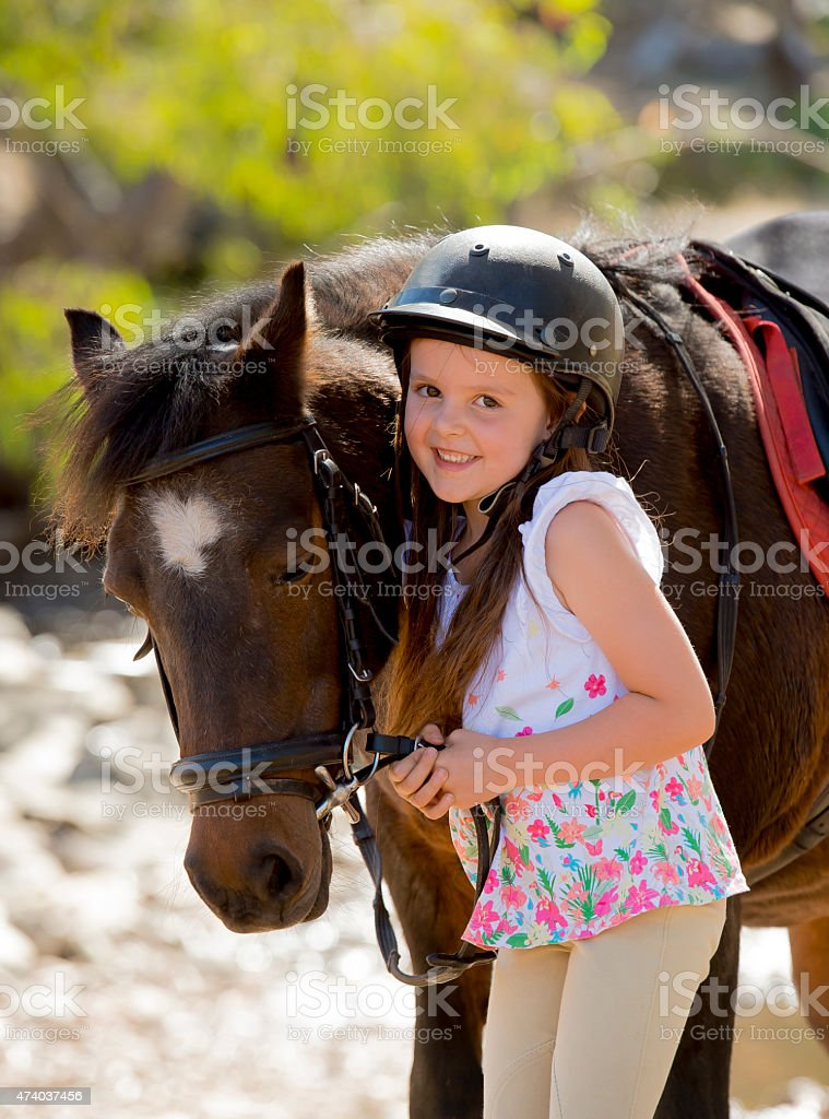 Little girl in jockey helmet next to a little pony stock photo