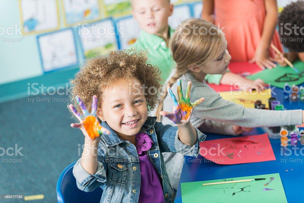 Little girl in kindergarten class doing art project stock photo