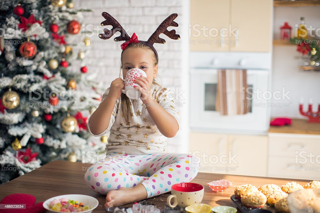 Little girl in kitchen for christmas eating muffins. stock photo