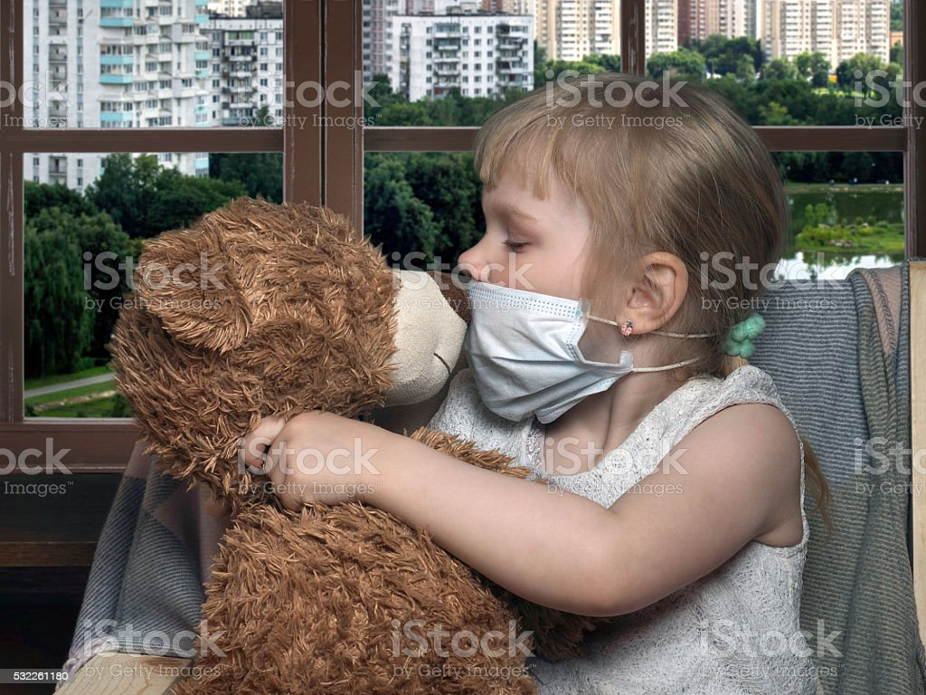Little girl in medical mask kissing toy bear stock photo