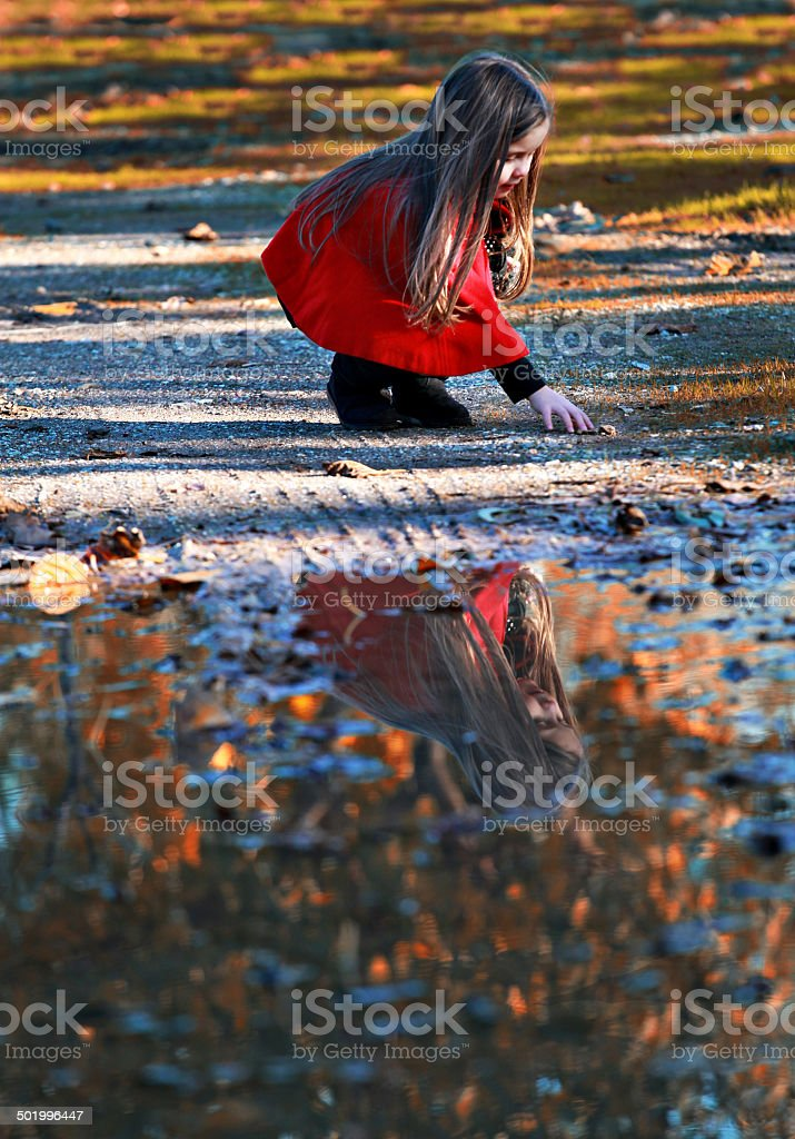 Little girl in nature and water reflection royalty-free stock photo
