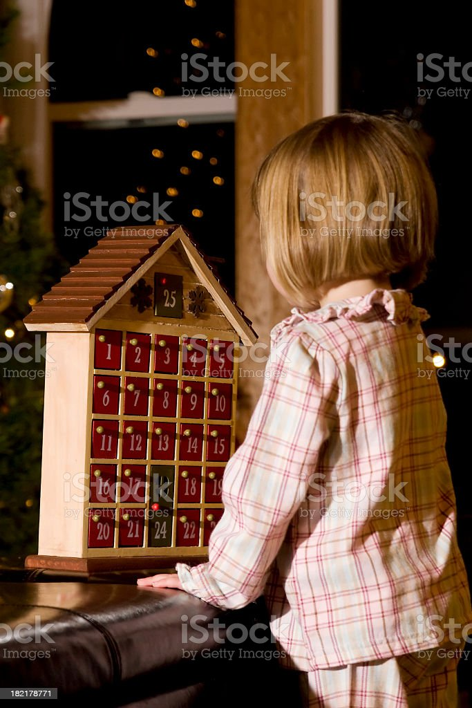 A little girl in pajamas playing with an advent calendar stock photo