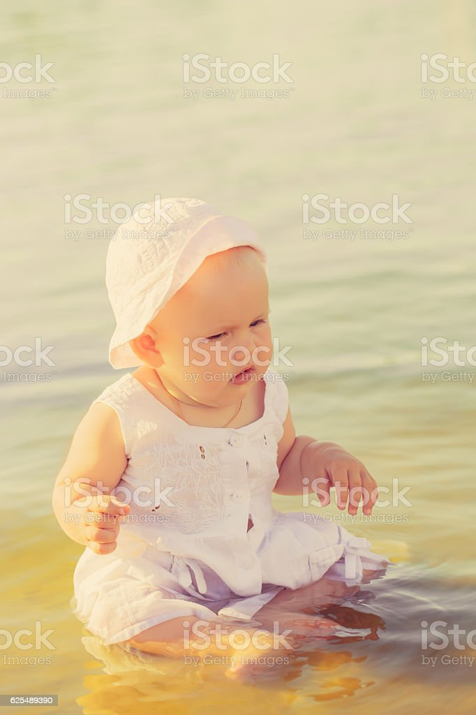 Little girl in panama sitting in the river stock photo