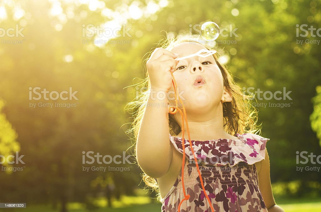 Little girl in park blowing bubbles stock photo