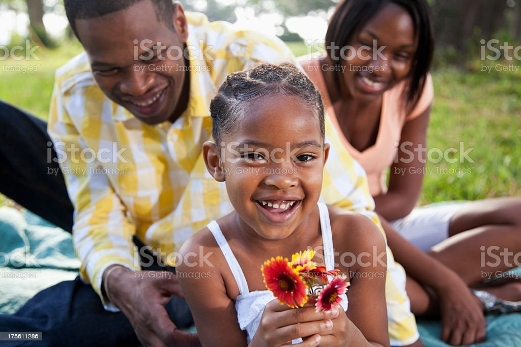 Little girl in park with parents stock photo