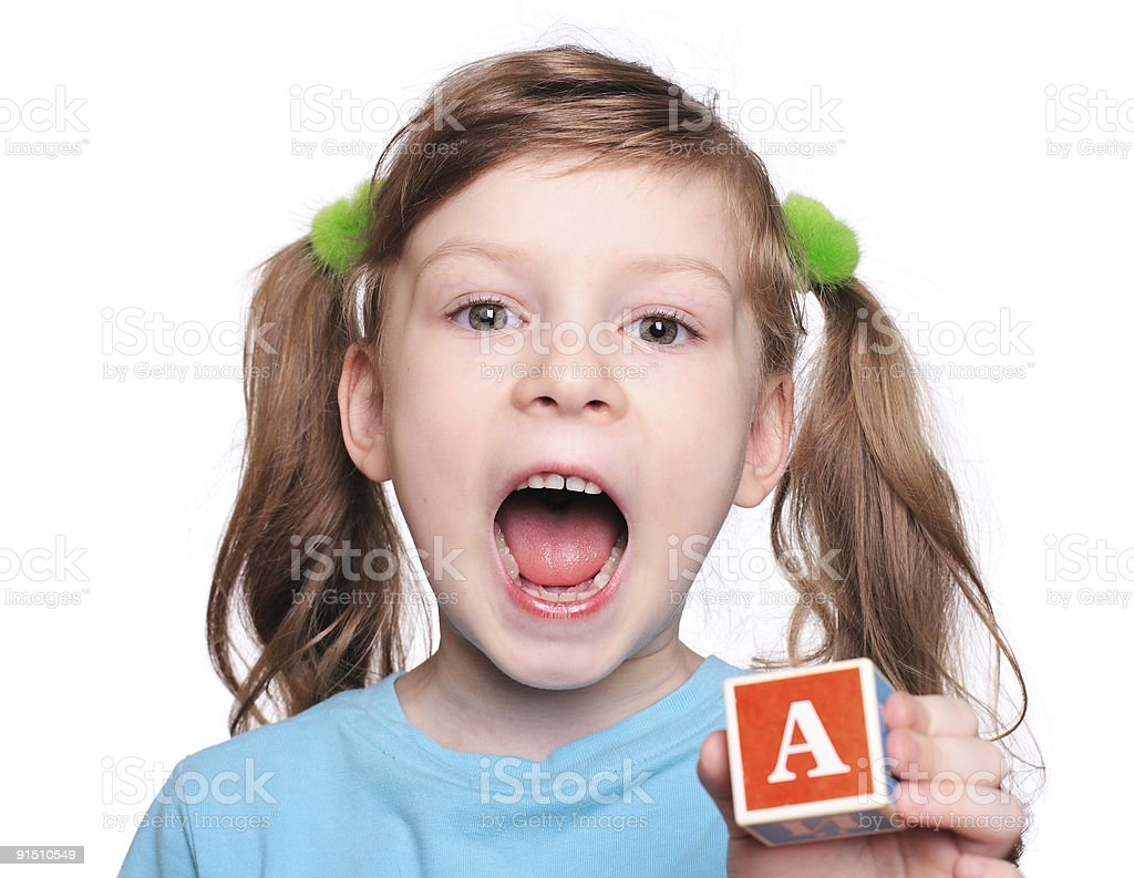 Little girl in pigtails holding letter block royalty-free stock photo