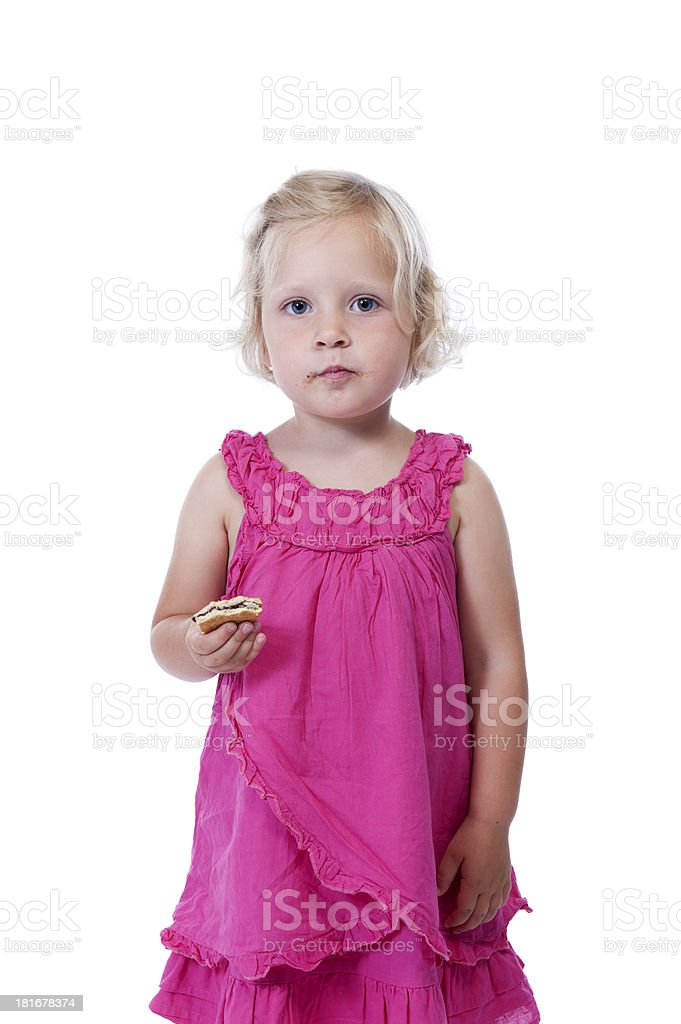 little girl in pink eating a biscuit, isolated on white royalty-free stock photo
