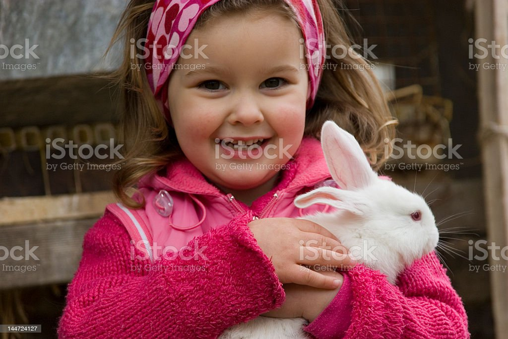 A little girl in pink holding hugging a white bunny royalty-free stock photo