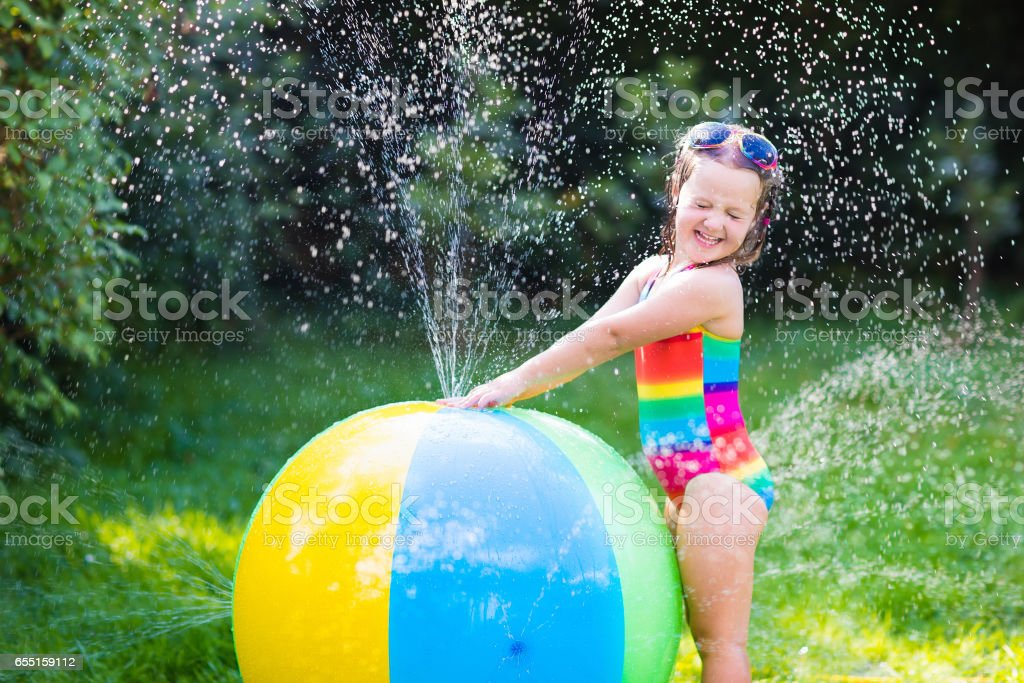 Little girl in playing with toy ball garden sprinkler royalty-free stock photo