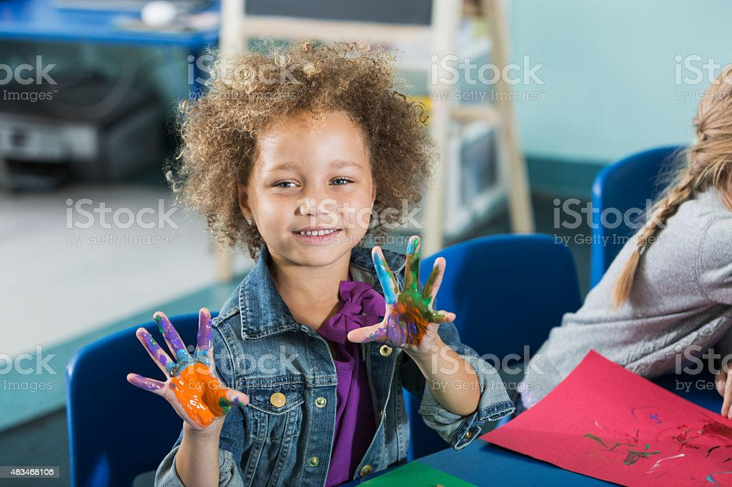 A cute, happy little girl in preschool, sitting at a table doing an...