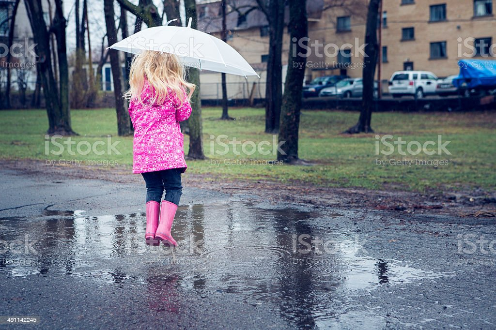 Little girl in puddle stock photo