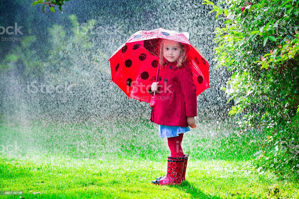Little girl in red jacket playing in autumn rain stock photo