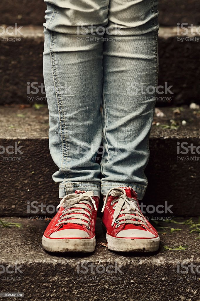 Little girl in red sneakers standing on the stairs stock photo