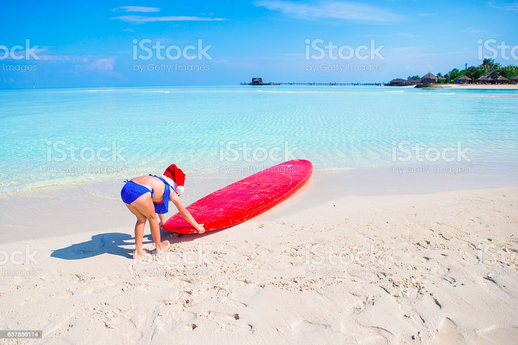 Little girl in Santa hat during beach vacation on tropical stock photo