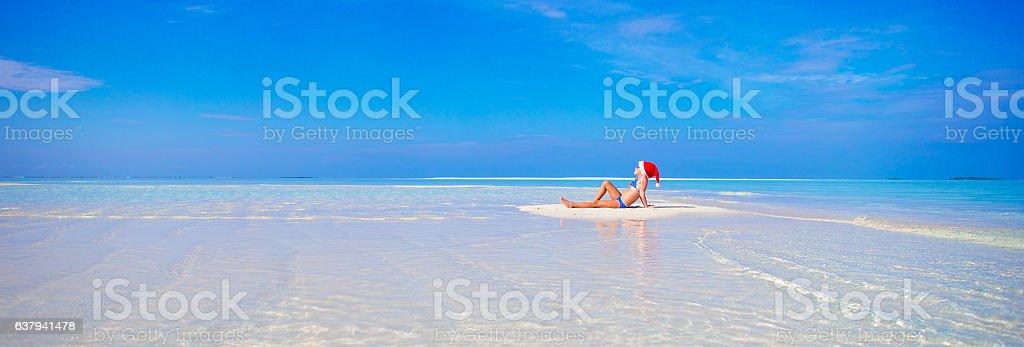 Little girl in Santa hat on white beach during Xmas stock photo