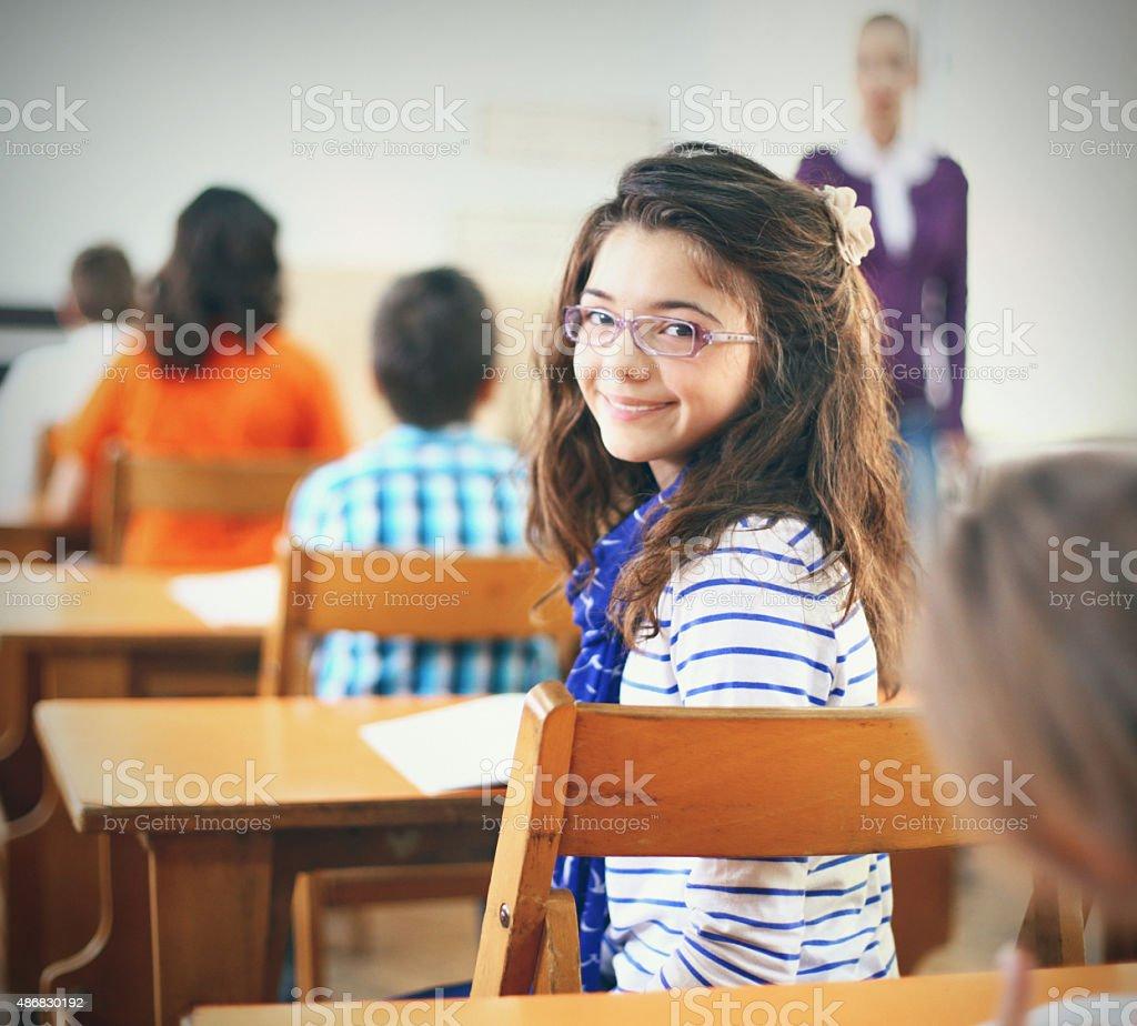Little girl in school class. stock photo
