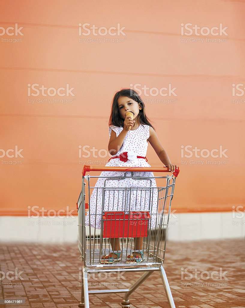Little girl in shopping cart with icecream stock photo