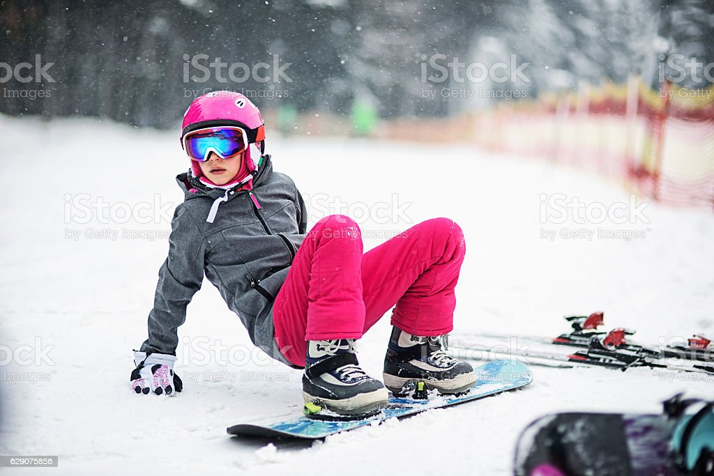 Little girl in snowboard lesson stock photo