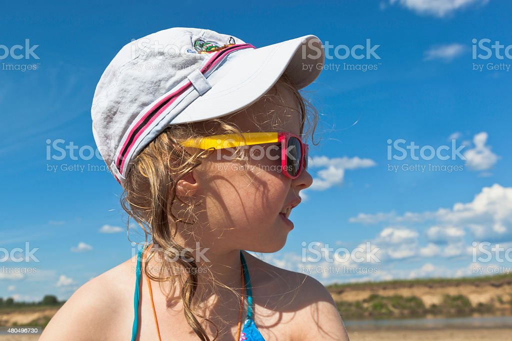Little girl in sunglasses on the beach looks away stock photo