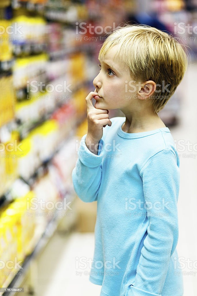 Little girl in supermarket tries to decide on a purchase royalty-free stock photo