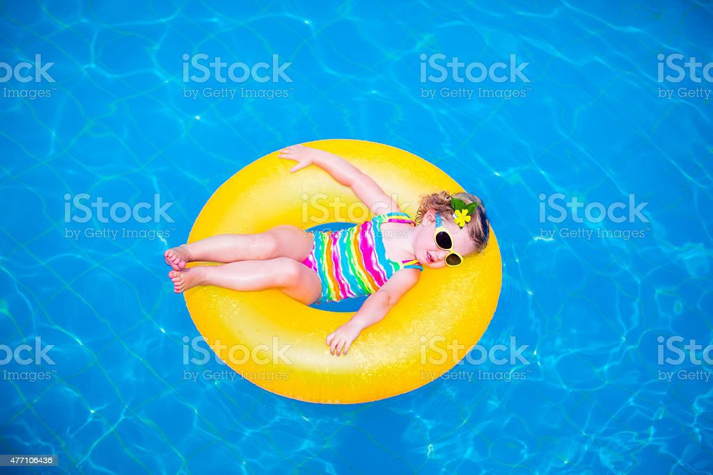 Little girl in swimming pool on inflatable ring stock photo