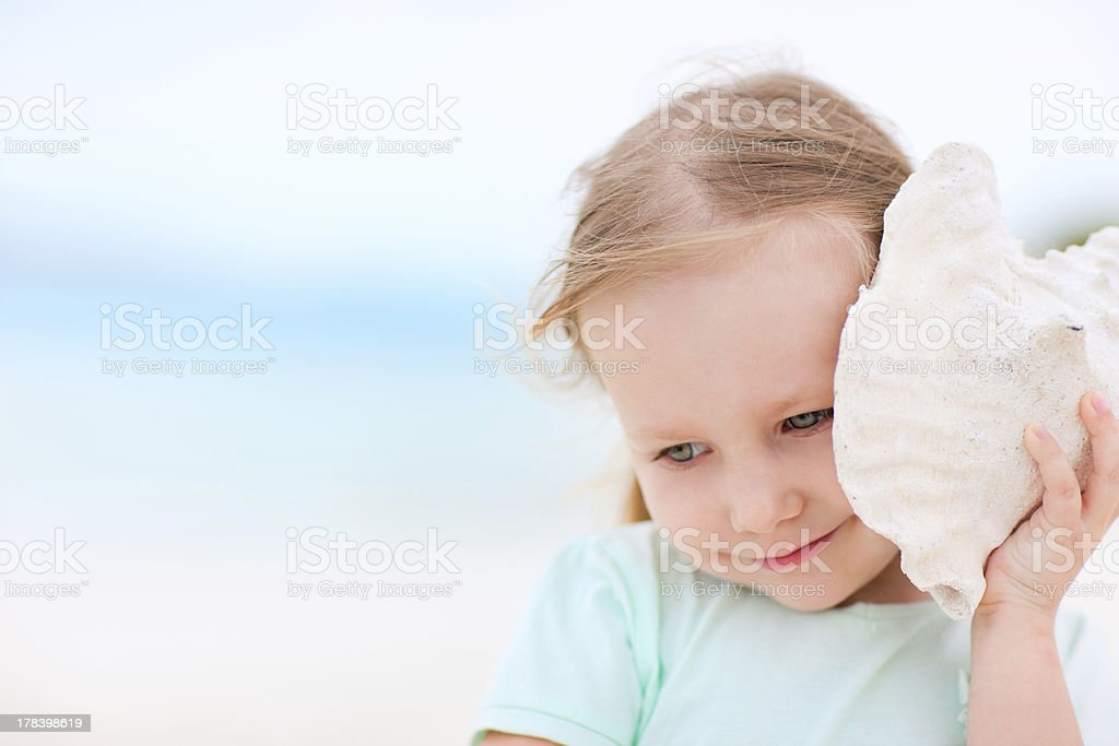 A little girl in teal holding a sea shell to her ear stock photo